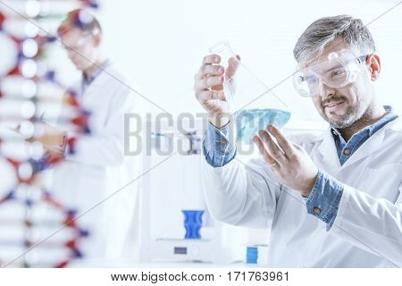 Chemist Holding Glass Vessel