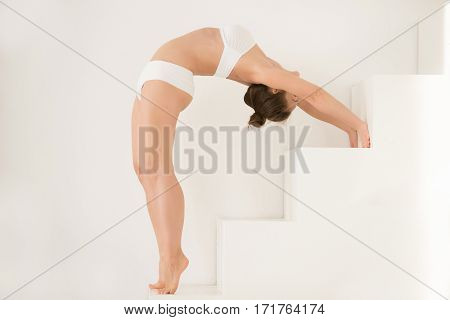 Young attractive lady practicing yoga on stairs, Ardha Chakrasana exercise, Standing Backward Bend pose, working out, wearing sportswear, sport bra, shorts, indoor full length, white color background
