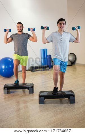 Two men doing step aerobic exercise with dumbbell on stepper in fitness studio