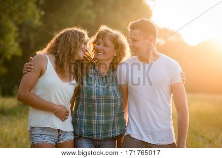 Cheerful happy caucasian family outdoors during summer sunset