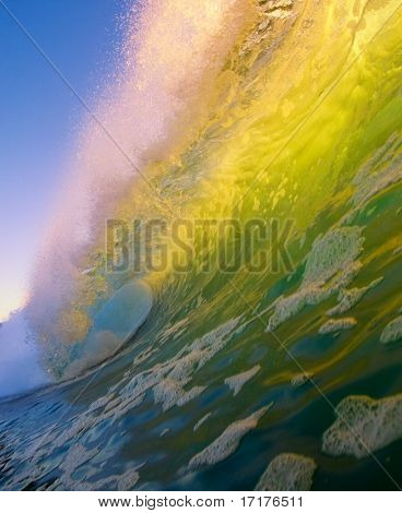 Large Green Wave Breaks in Ocean at Sunset