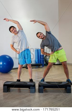 Portrait of two men doing aerobic exercise with stepper on fitness studio