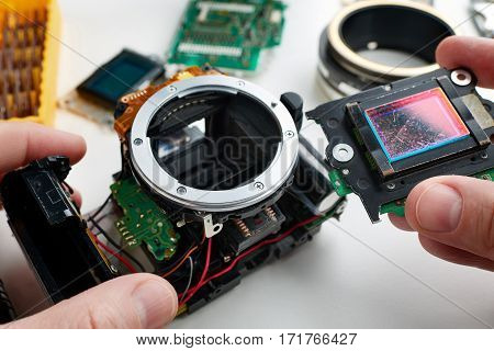 Old Scratched Image Sensor Digital Slr Camera In Hands Of Service Engineer