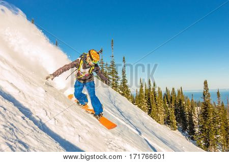 Freeride Snowboarder Slides Down A Steep Slope At Dawn