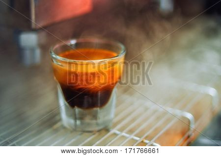 Cup of the espresso in the grid of coffee machine in a hot pair. Beautiful background.
