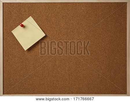 Blank yellow sticky note pinned on a cork bulletin board