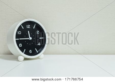 Closeup black and white alarm clock for decorate in a quarter to twelve or 11:45 a.m. on white wood desk and cream wallpaper textured background with copy space
