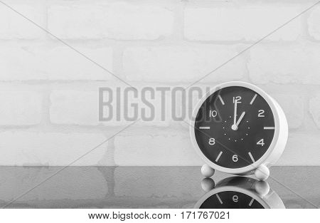 Closeup black and white alarm clock for decorate in 1 o'clock on black glass table and white brick wall textured background in black and white tone with copy space