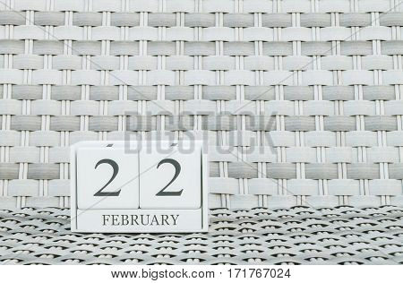 Closeup surface white wooden calendar with black 22 february word on blurred weave wood chair textured background with copy space in selective focus at the calendar