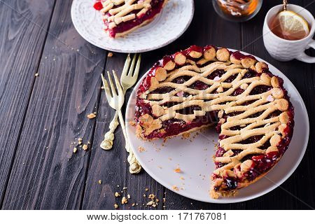 Tart, pie, cake with jellied fresh cranberries, bilberries and winter spices on a brown wooden background. Copy space