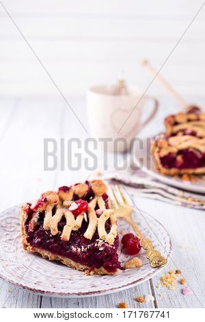 Delicious Homemade Cherry Pie with a Flaky Crust on white wooden background, copy space