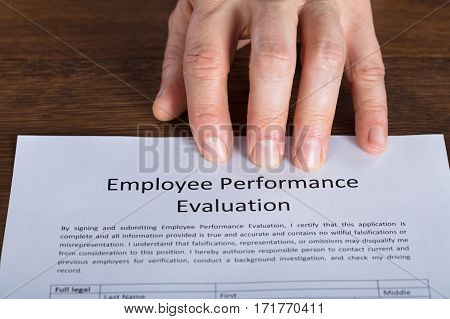 Close-up Of A Person Hand On Performance Evaluation Form At Wooden Desk