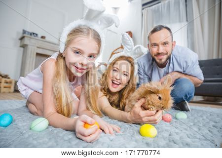 Family playing with rabbit and Easter eggs while lying on carpet at home