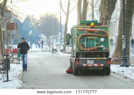 ZAGREB CROATIA - JANUARY 15 2017 : A man walking next to the street sweeper machine in city center in Zagreb Croatia.