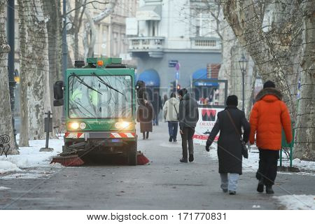 ZAGREB CROATIA - JANUARY 15 2017 : People walking in Zrinjevac park next to the street sweeper machine in Zagreb Croatia.