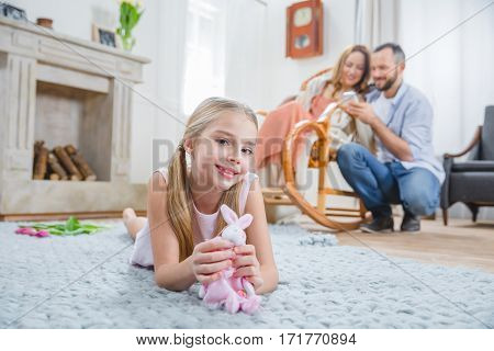 Cute little girl playing with toy rabbit and her parents relaxing
