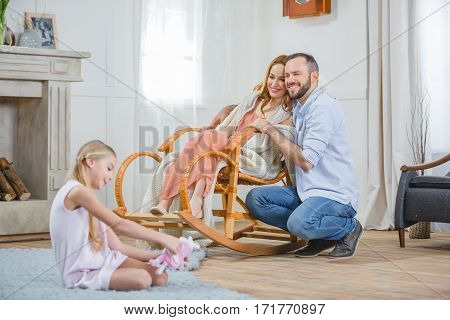 Happy young family of three spending time together at home