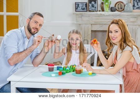 Happy young family sitting at table and painting Easter eggs