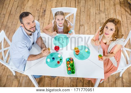 Top view of happy family at the table painting Easter eggs together