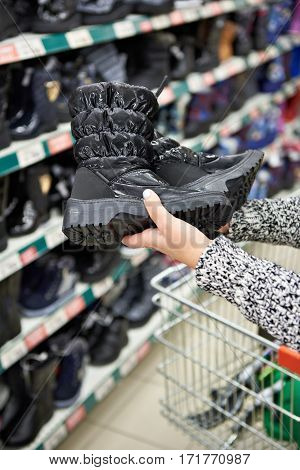 Winter Boots In Hands Of Women Customers At Store