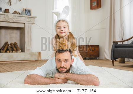 Father and daughter playing with rabbit on white fluffy carpet at home