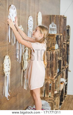 Side view of cute little girl decorating room with white decorative dreamcatchers