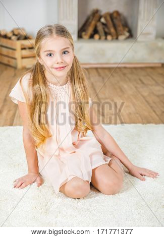 Cute little girl sitting on white carpet and smiling at camera