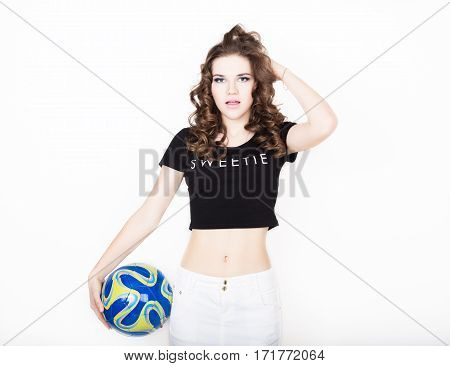 Young beautiful curly girl with professional make-up, holding a ball.