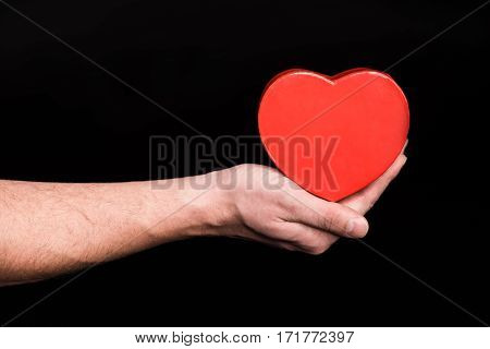 Close-up partial view of male hand holding heart sign on black