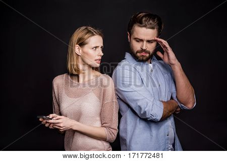 Young woman using smartphone and talking to man on black
