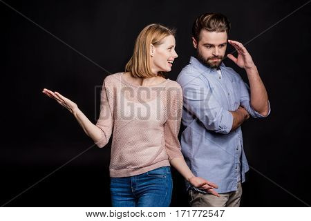 Young beautiful woman gesticulating to pensive man on black