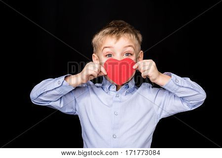 Cute little boy hiding lips with red paper heart and looking at camera on black