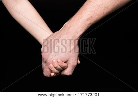 Close-up partial view of father and little child holding hands on black