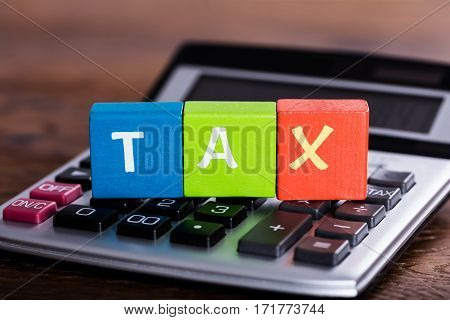 Close-up Of Colorful Blocks With Word Tax Placed Over Calculator