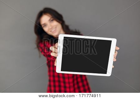 Shallow depth of field. Empty screen digital tablet computer isolated on grey background. Girl holding tablet with black display
