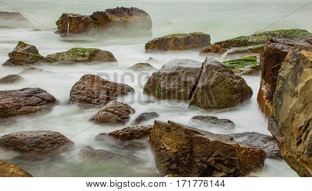 A rocky ocean coastline slow exposure with large rocks covered in moss in Vung Lam Bay Vietnam.