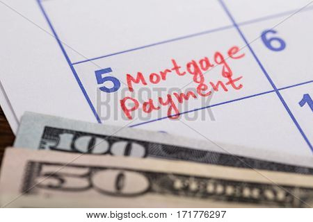 Close-up Of Mortgage Payment Reminder Written On Calendar With Banknotes