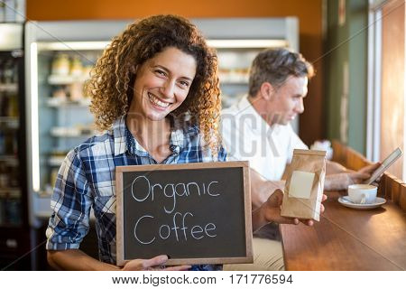 Woman in café holding a board that reads Organic Coffee
