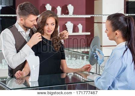 I think I like it. Professional jeweler standing with a young loving couple fitting a necklace at the store couple buying jewelry profession luxury lifestyle festive anniversary present couple love