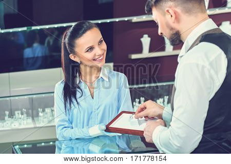 Advising her client. Professional jewelry store clerk smiling joyfully showing precious diamond ring to her customer profession positivity working jewelry bridal choosing buying engagement concept