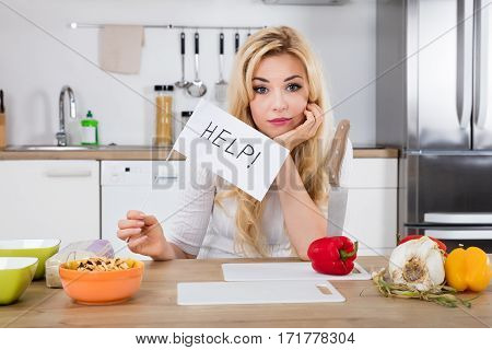 Young Unhappy Woman Holding Help Flag For Cooking In Kitchen At Home