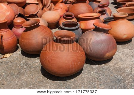 Many clay pots of baked clay kept in the sun to dry. Traditional handmade pitchers on the island of Sri Lanka