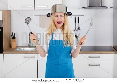 Portrait Of A Frustrated Woman Wearing Cooking Pan Holding Spoon In Kitchen At Home