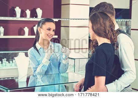 Her special customers. Toned shot of a beautiful young couple choosing jewelry at the store buying necklace from a professional jeweler occupation service assistance choice luxury love couples concept