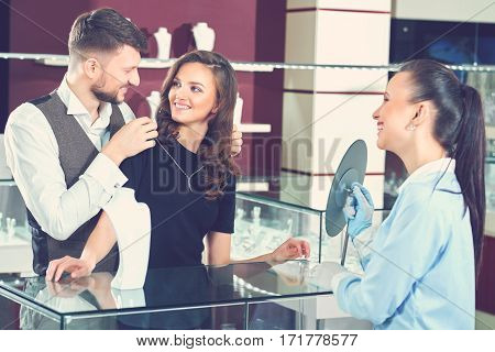 We will take this one Happy young couple smiling at each other while trying a necklace at the jewelry store clients customers buying shopping lifestyle relationships wife husband anniversary gift.