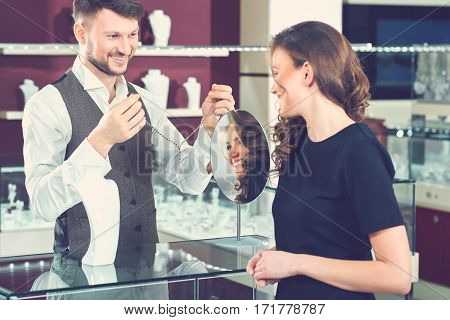 Try this one. Professional jewelry store clerk showing a necklace to his female client profession job occupation career positivity helping selling salesman businessman customer consumerism concept
