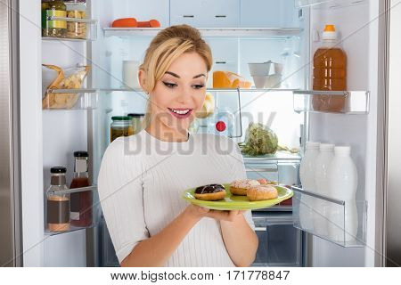Young Woman Standing Near Refrigerator Eating Donut From Plate