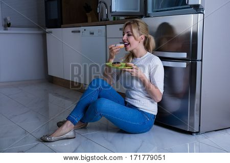 Young Happy Woman Eating Sweet Food Near Refrigerator In The Kitchen