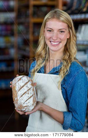 Portrait of smiling female staff holding bread in super market