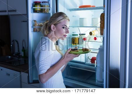 Suspicious Woman Taking Sweet Food Secretly From Fridge In The Kitchen